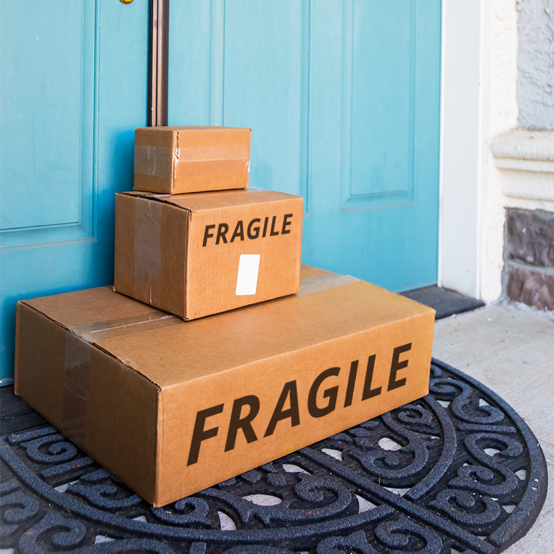 stack of three parcels at front door with fragile written on box in black letters