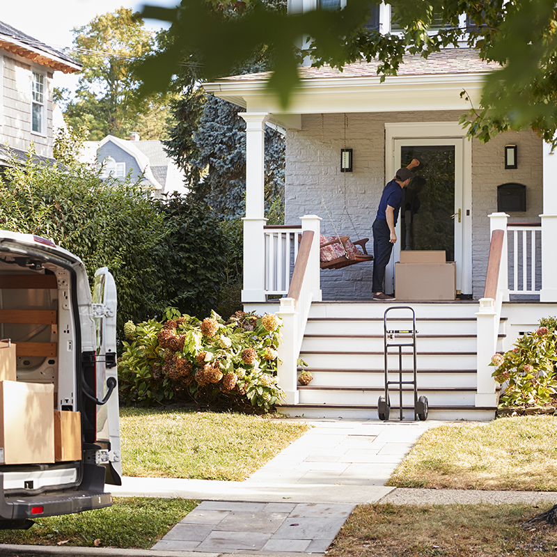 courier knocking on residential door to deliver two mailed parcels