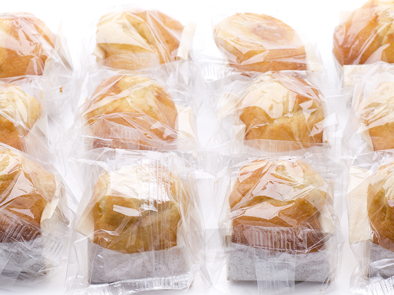 individually flow wrapped muffins on white background