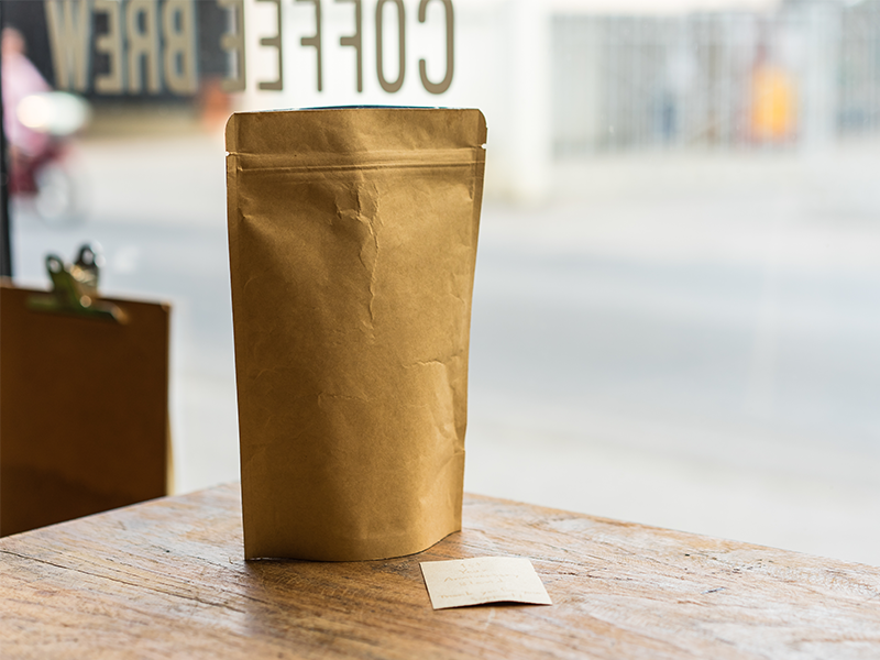 plain brown paper pouch bag with resealable zipper on table near window inside coffee shop