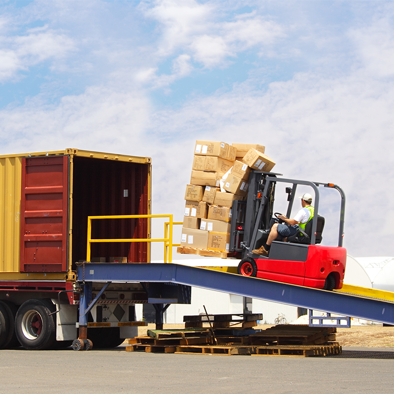 boxes being loaded in a shipping truck by a forklift