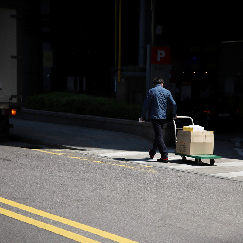 courier rolling packages on trolley in city street