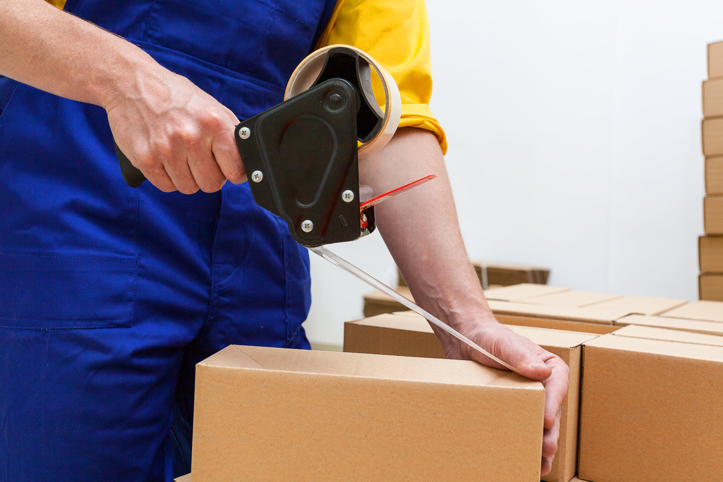 hands of a man sealing cardboard box with hand taper