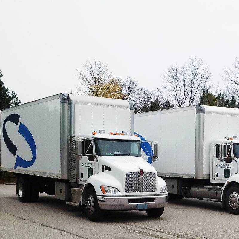 pair of white transport trucks with crawford branding