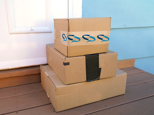 three printed water-activated tape boxes stacked at front door step