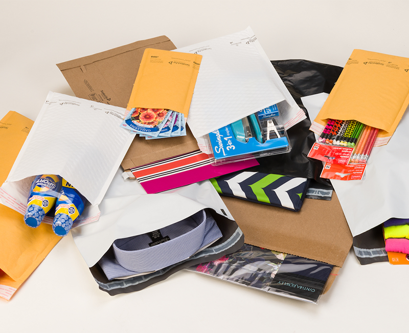 group of jiffy packaging mailers with various products inside on white background