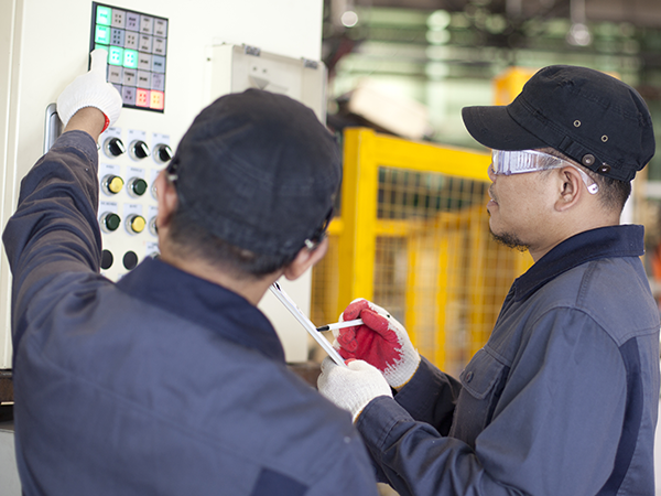 two service technicians standing next to packaging machine training operators
