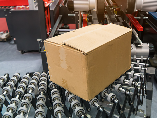 cardboard box on roller conveyor attached to case sealer in packaging facility