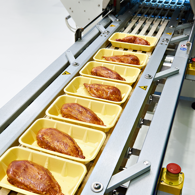 cooked chicken packed in yellow trays on top seal packaging machine with white background