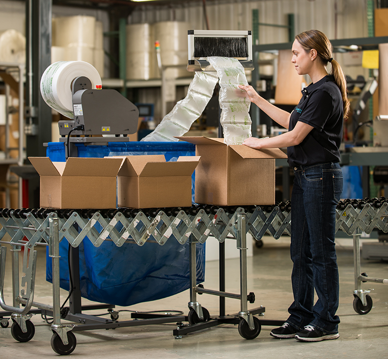 woman packaging cardboard boxes on conveyor with sealed air fill air rocket machine air pillows