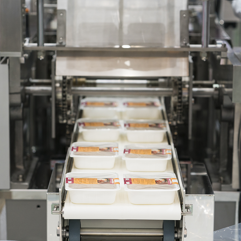 empty white trays with printed top seal film exiting outfeed conveyor of top seal machine