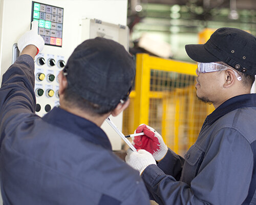 two men standing in front of packaging machine wearing work clothes and safety gear