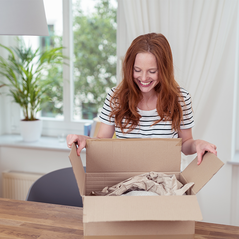 woman opening parcel box to see product packaged with paper void fill packaging