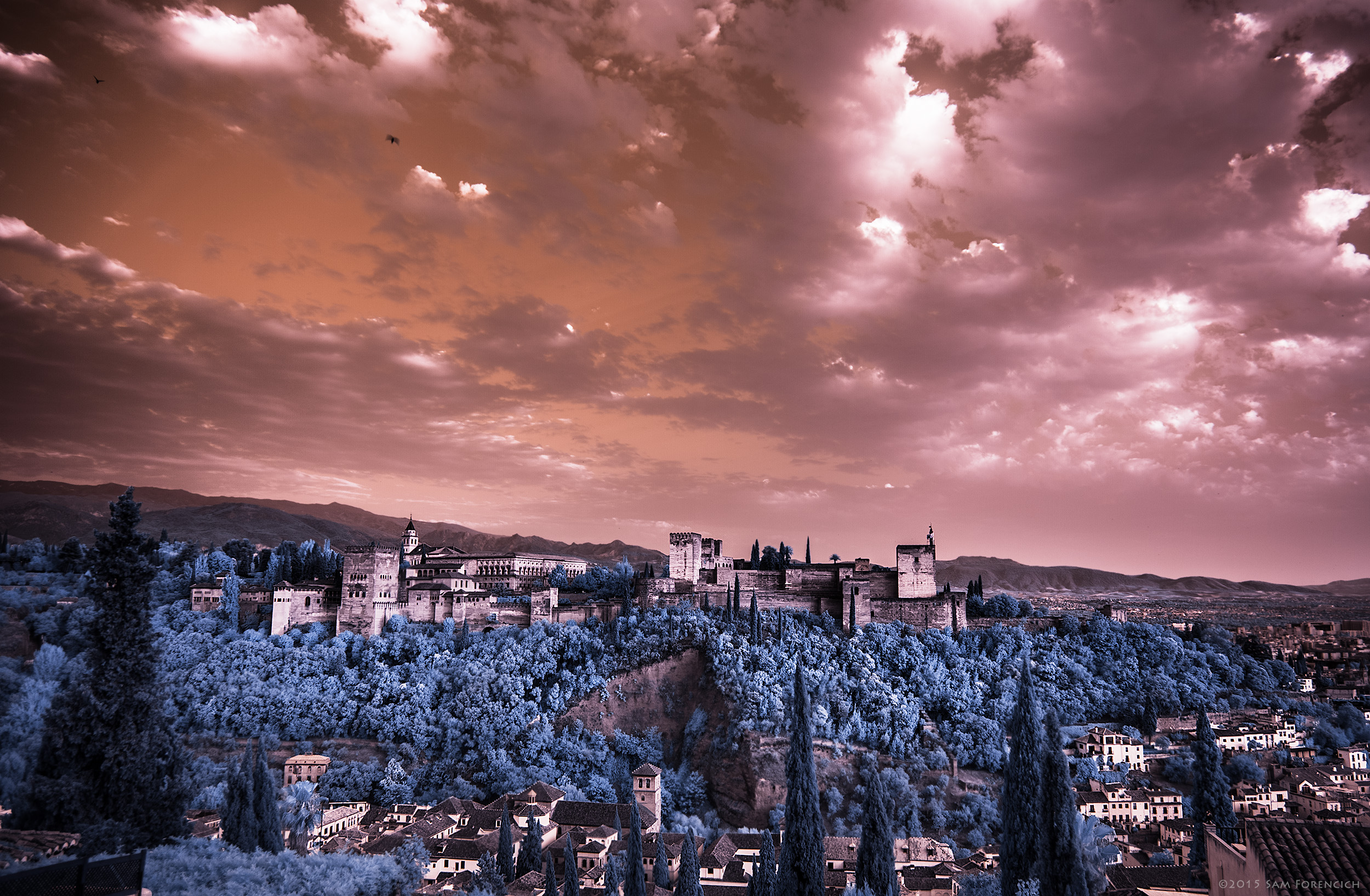 The Alhambra, a Moorish palace and fortress overlooks the city of Granada, Andalusia, Spain. The palace was built primarily between 1238 and 1358, during the reigns of Ibn al-Ahmar, founder of the Nasrid Dynasty and his successors. Photographed from Mirador de San Nicolas. Channel swapped infrared, IR converted Canon 5D Mark II.  ©2015 Sam Forencich