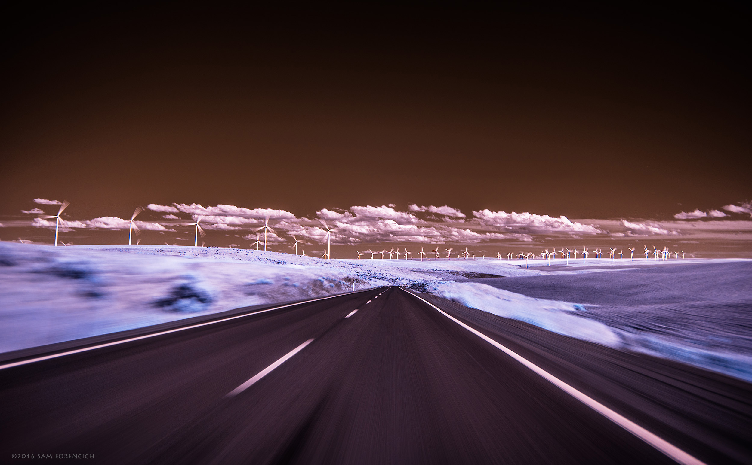A country road winds through the windmill farms of the Columbia Plateau region of Central Oregon. Still image from Invisible Oregon time-lapse sequence. IR converted Nikon D750. © 2016 Sam Forencich