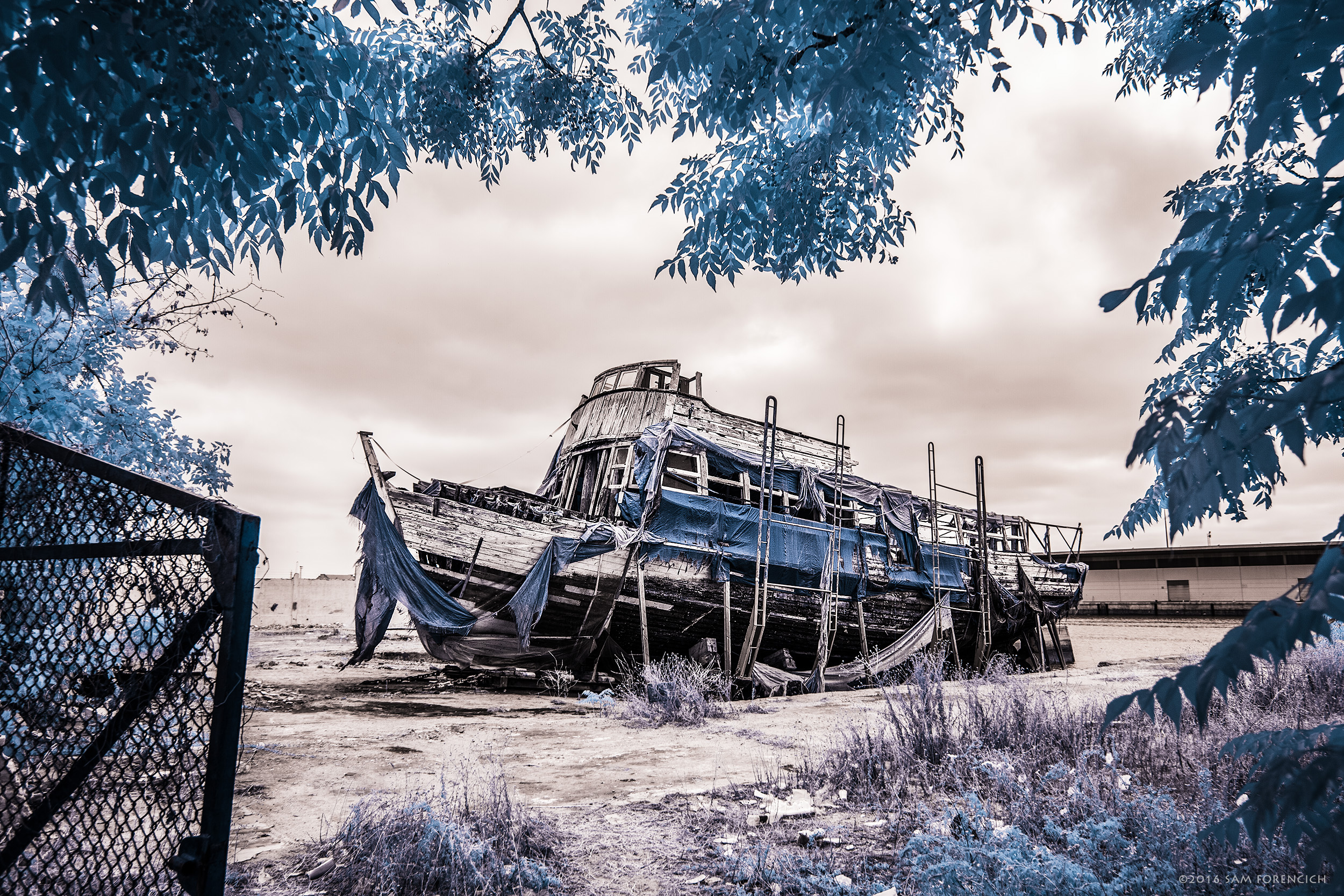 A formerly sunken vaporetto (water bus/taxi) awaits it's fate in dry dock near the harbor of El Puerto de Santa Maria on the southern Atlantic coast of Spain. IR converted Canon 5D Mark II. © 2015 Sam Forencich