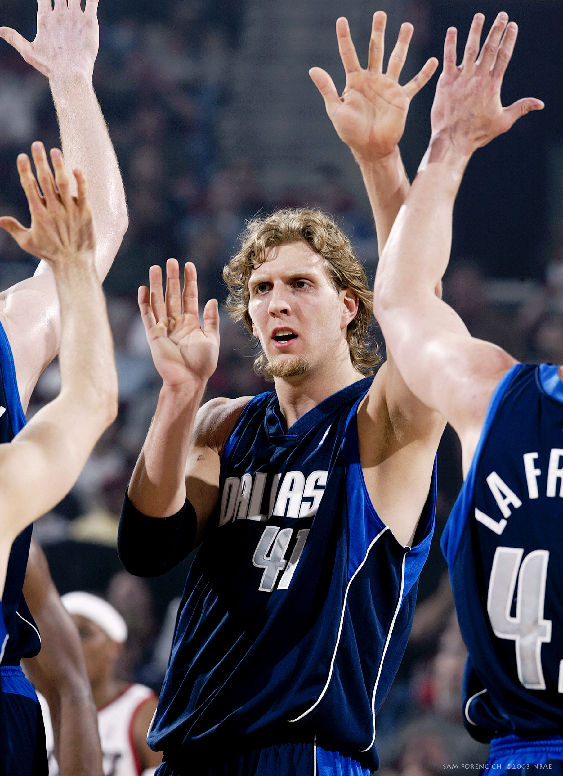Portland, OR - Dirk Nowitzki #41 of the Dallas Mavericks high-fives his teammates after the play against the Portland Trail Blazers in Game three of the Western Conference Quarterfinals during the 2003 NBA Playoffs at The Rose Garden on April 25, 2003. Digital 35mm, arena strobe lighting.  Sam Forencich ©2003 NBAE