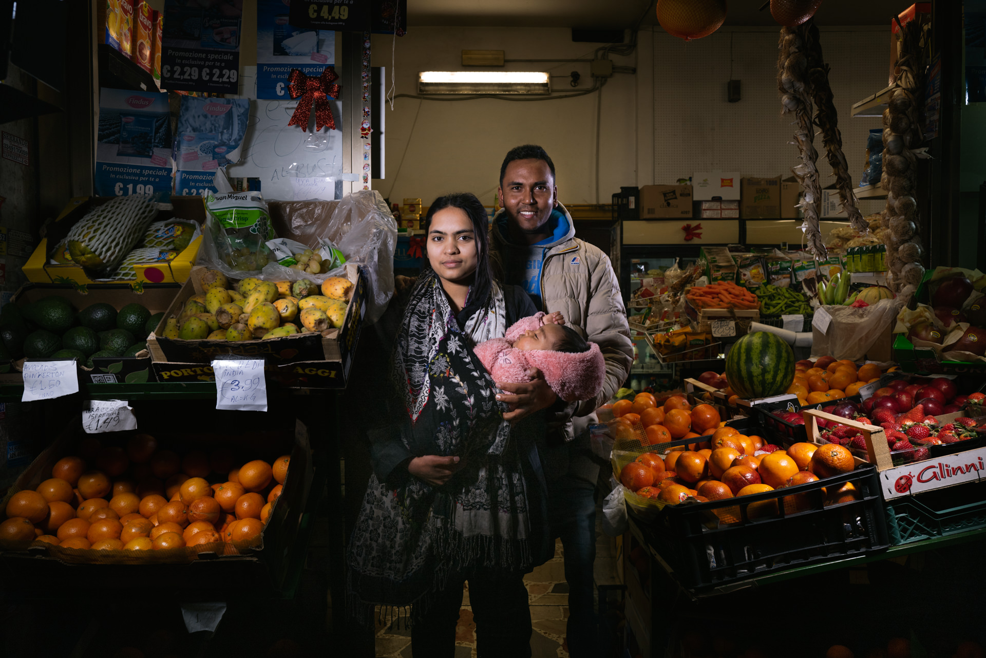A Environmental Portrait shot in Rome to Al Amin and his family in their fruit shop at Pigneto. Ambient light mixed with 2 led lights. Aperture f5.6 @400 iso