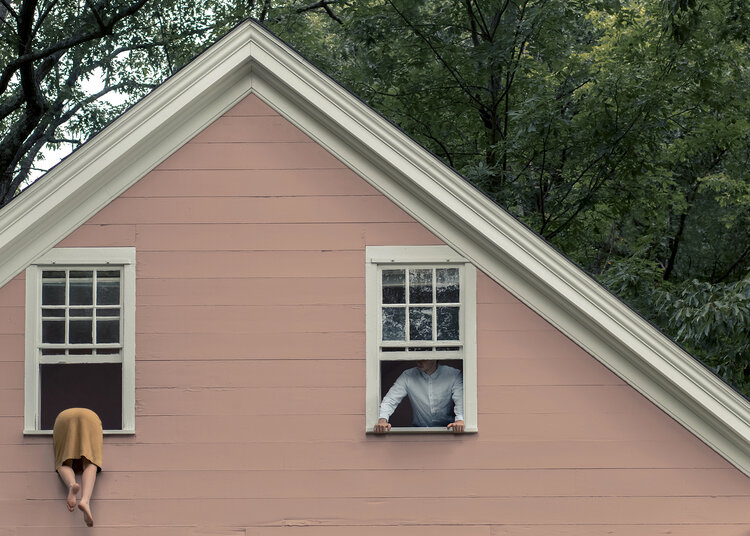 A photo of the front of a house with a woman's butt-half hanging out a window.