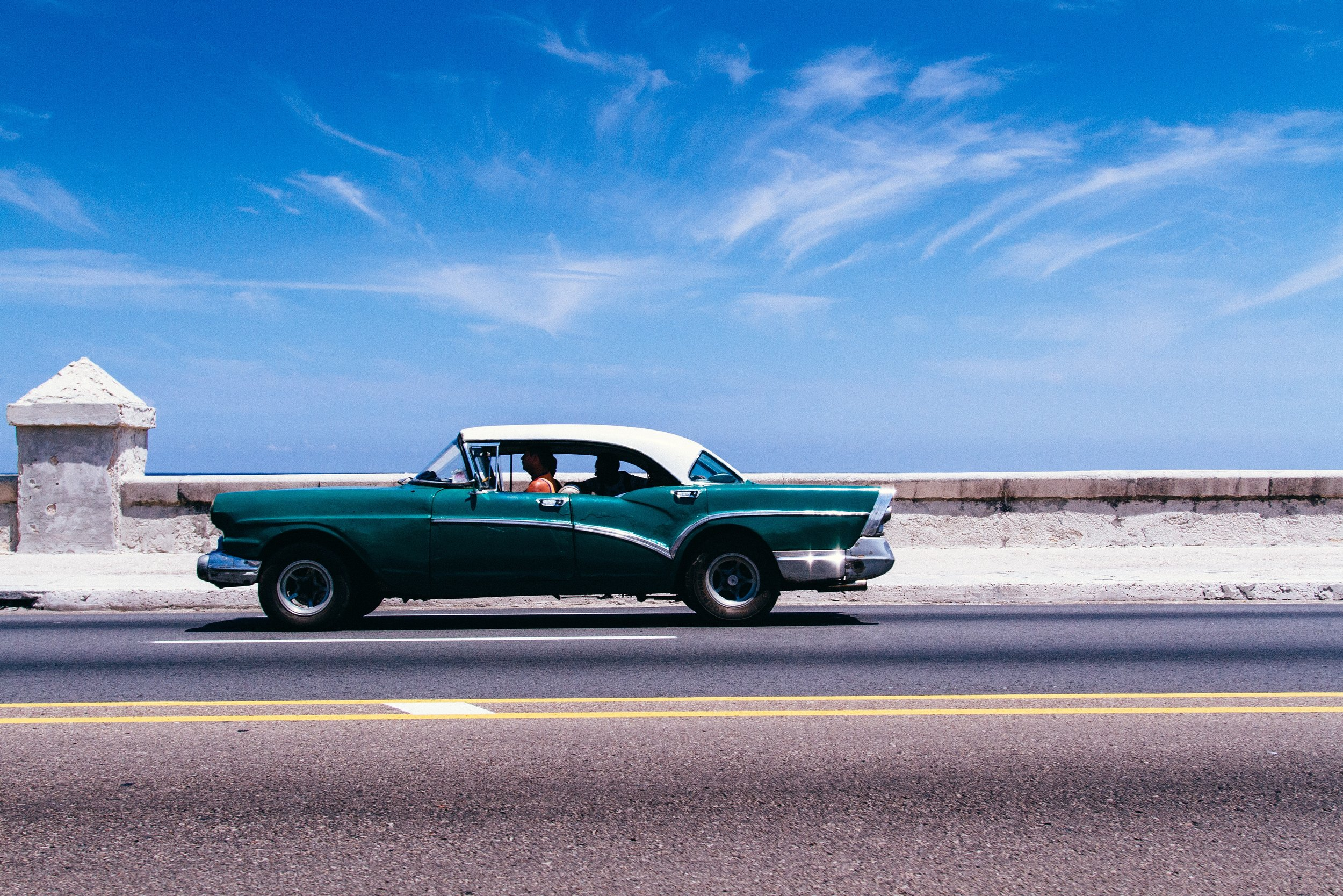 A vintage convertible drives by in Havana, Cuba.