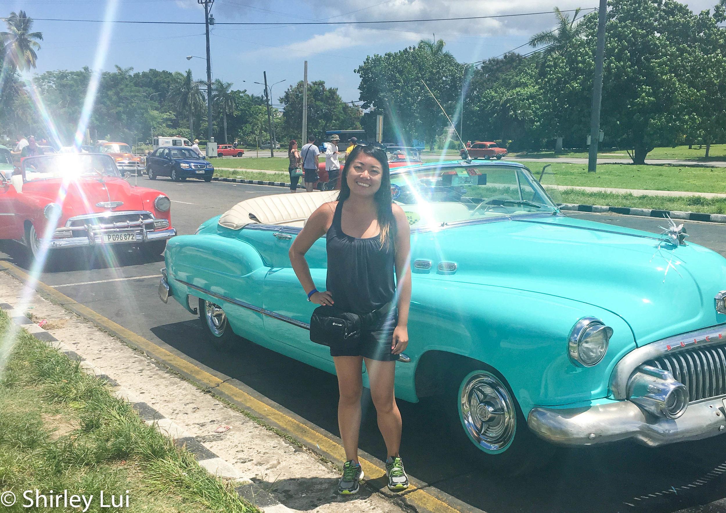 Me posing by a light blue convertible in Havana, Cuba.