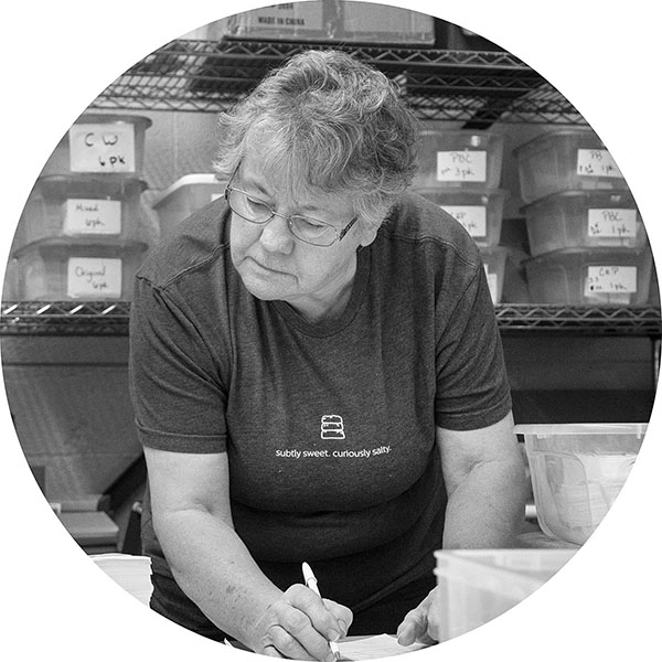 """Joan   Joan came to Kayak looking for a part time position. So much for that! She jumps in when and where needed with her incredible commitment to the quality of both the cookies and their packaging. Her undying motto of """"You have to be flexible"""" could not be more perfect for an ever changing and growing business. Her engineering skills, common sense, and wide experience help us navigate our way each and every day.  When not at Kayak, Joan is a meticulous gardener and devoted grandmother to Jonathan!"""