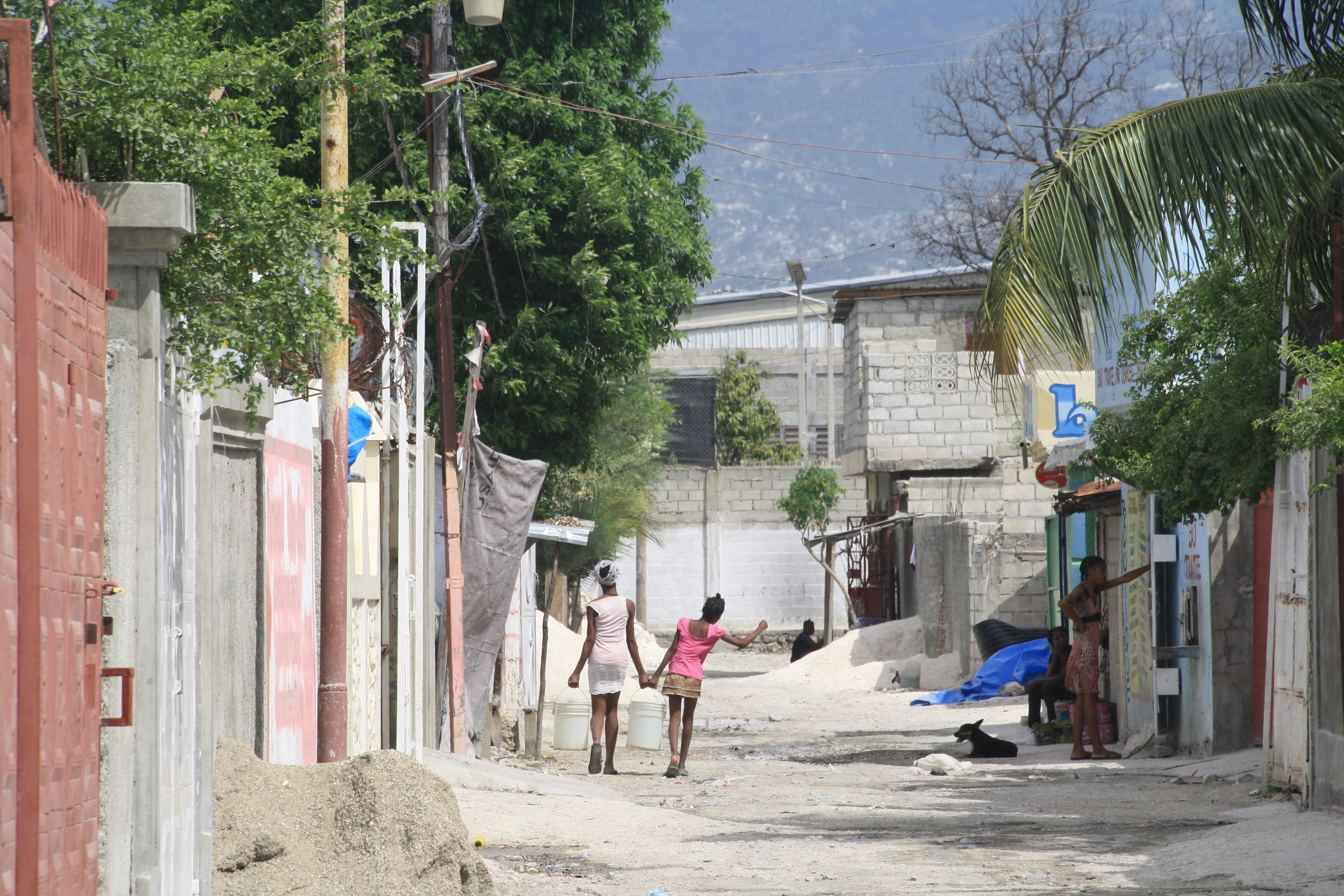 Two young women carry water back to their home from the local well. Image: Lorelle Shea