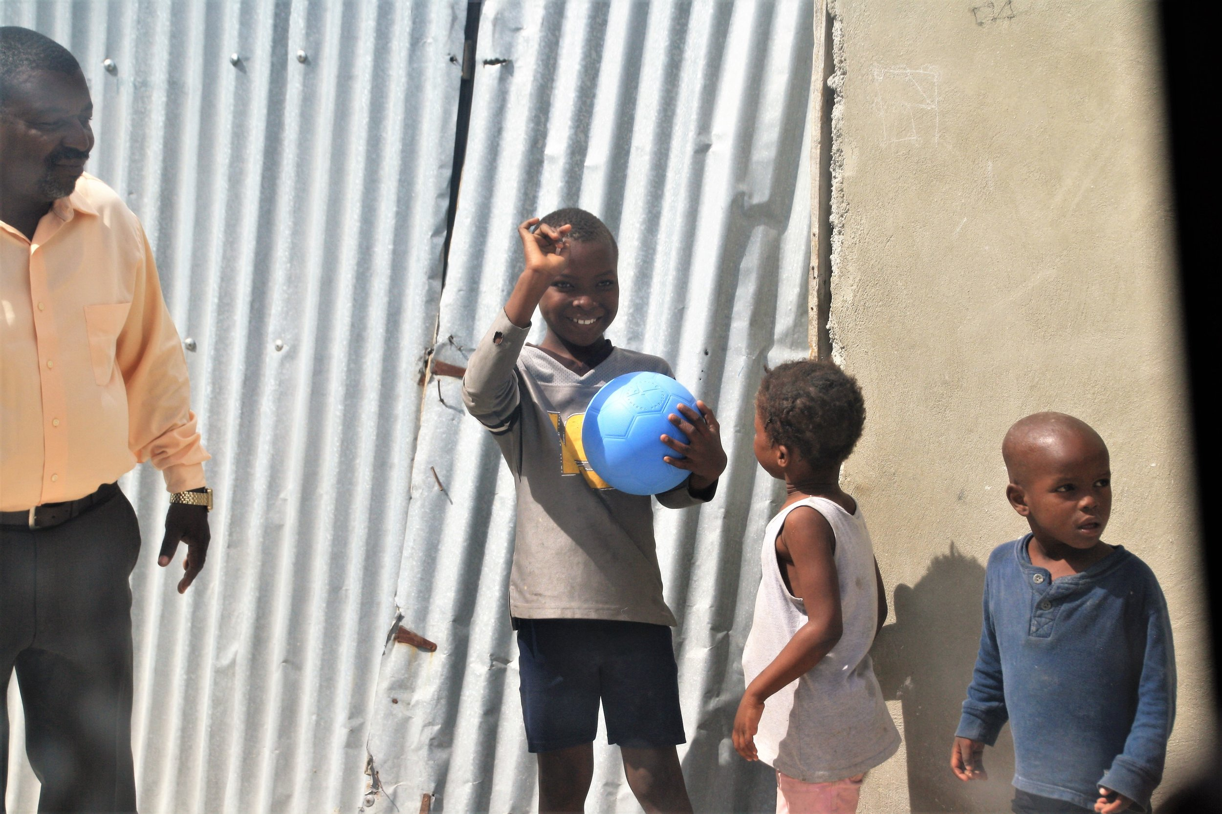 A young boy smiles and waves,delighted by his new soccer ball. Image: Lorelle Shea