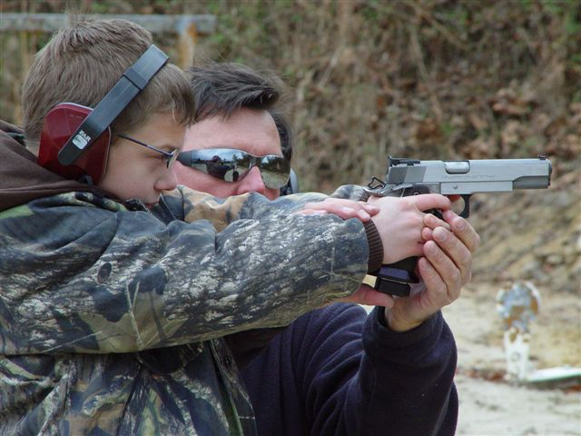 Above: D.R. coaches an 8 year old on proper handling of the Semi-Auto Pistol...