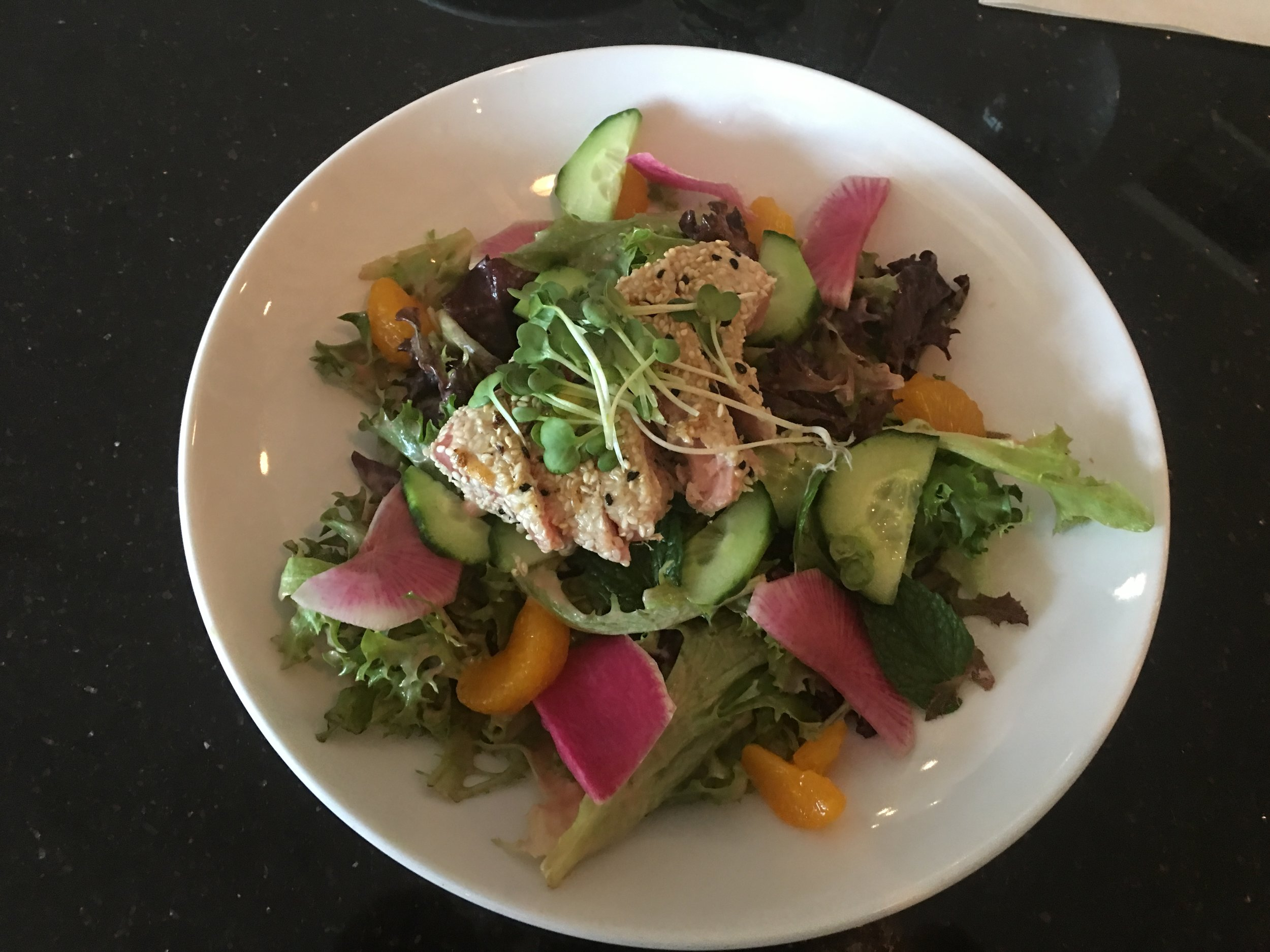Sesame Crusted Seared Ahi Salad : Ahi, Tuna , Watermelon Radish, mandarin orange, English Cucumber, radish sprouts, basil, mint, mixed lettuce with a Blood Orange vinaigrette Dressing