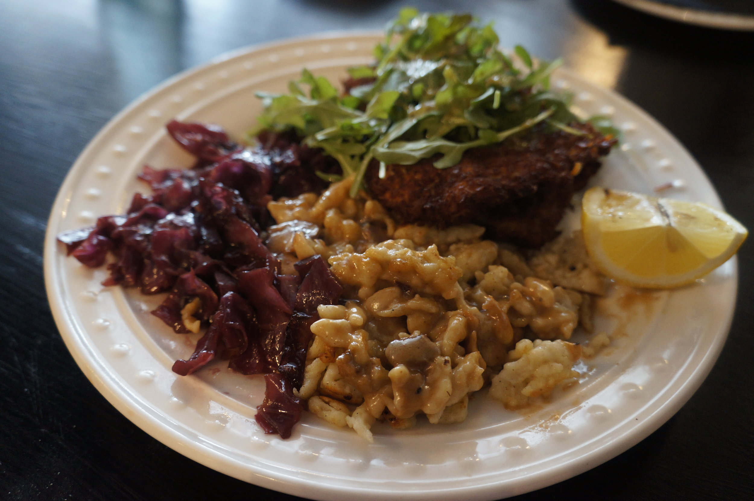 The Haus Schnitzel —   Thinly pounded, coconut battered and fried pork loin served with spaetzle, red cabbage, topped with arugula and mint dressing.