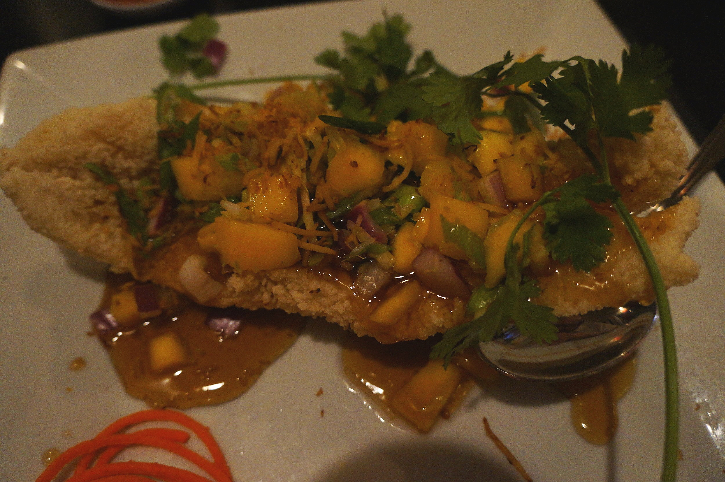 Crispy Mango Fish - One crispy ten oz fish filet topped with ripe mango, onion, ginger, lemongrass, toasted coconut flakes & lime drizzled with a sweet tamarind sauce.