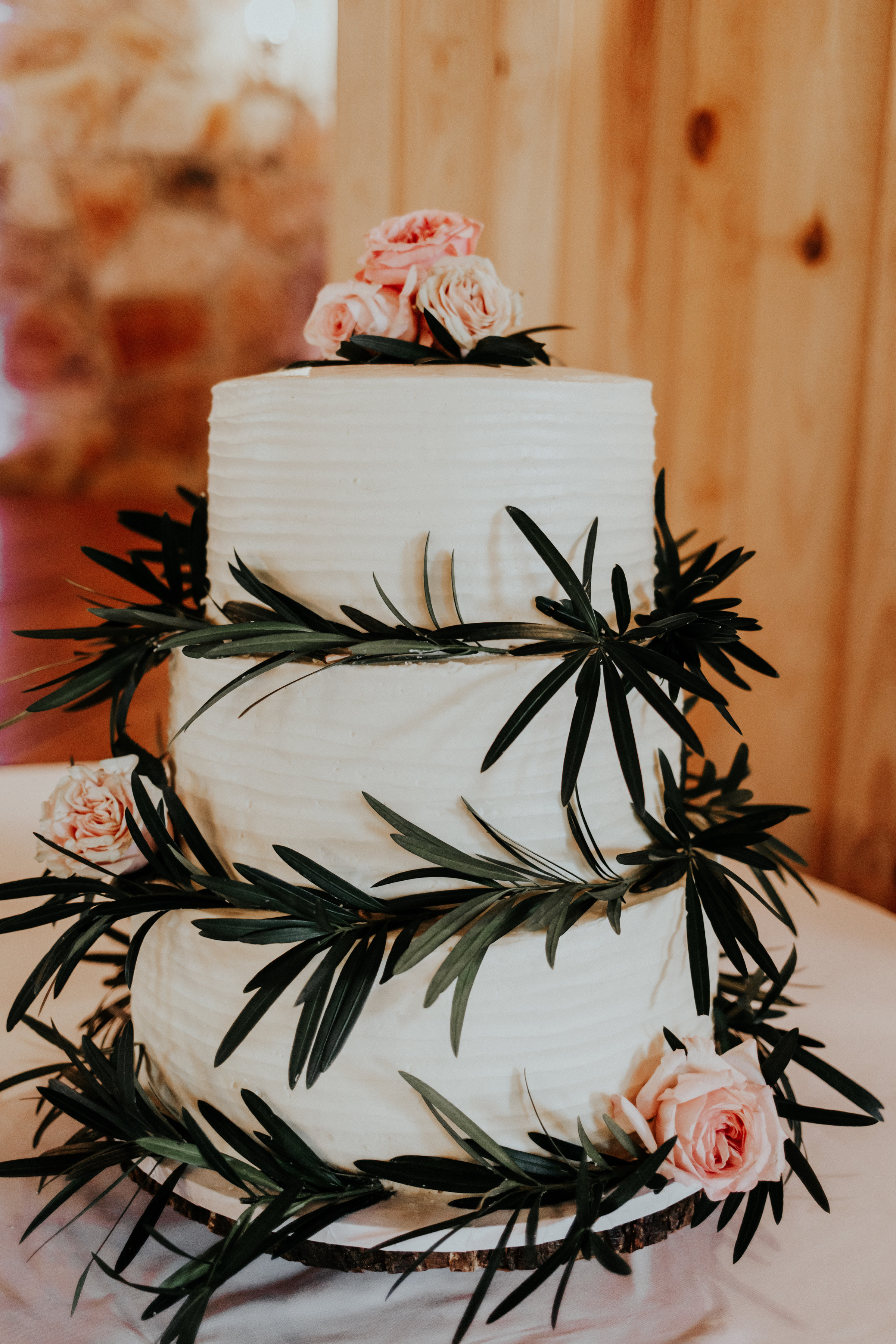 A simple butter cream cake was adorned by greenery and fresh blooms!