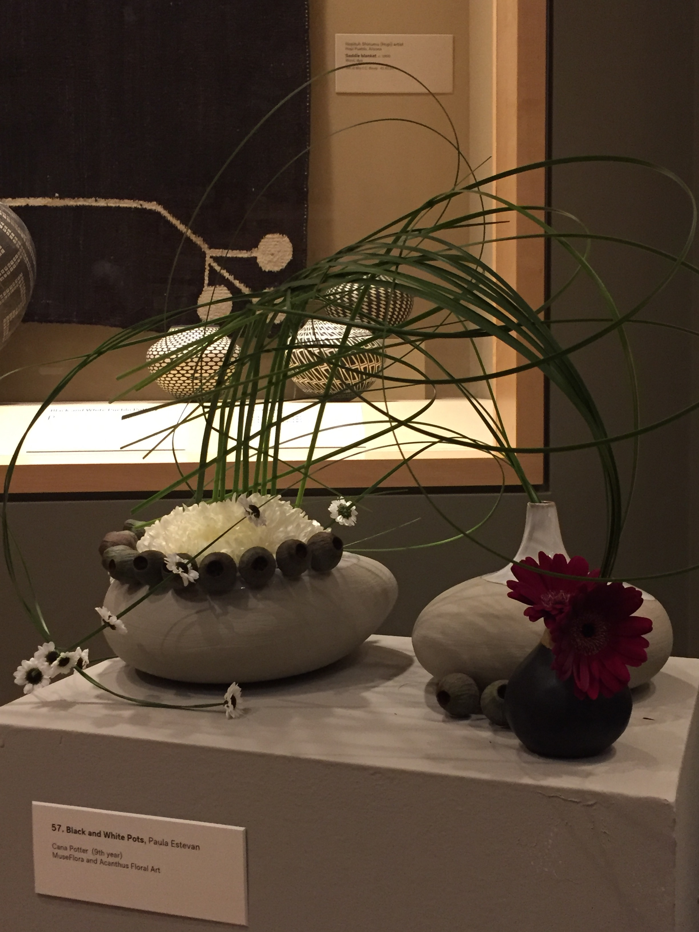 Woven bear grass, white chrysanthemums, red gerberas, black and white mum poms, and eucalyptus pods.