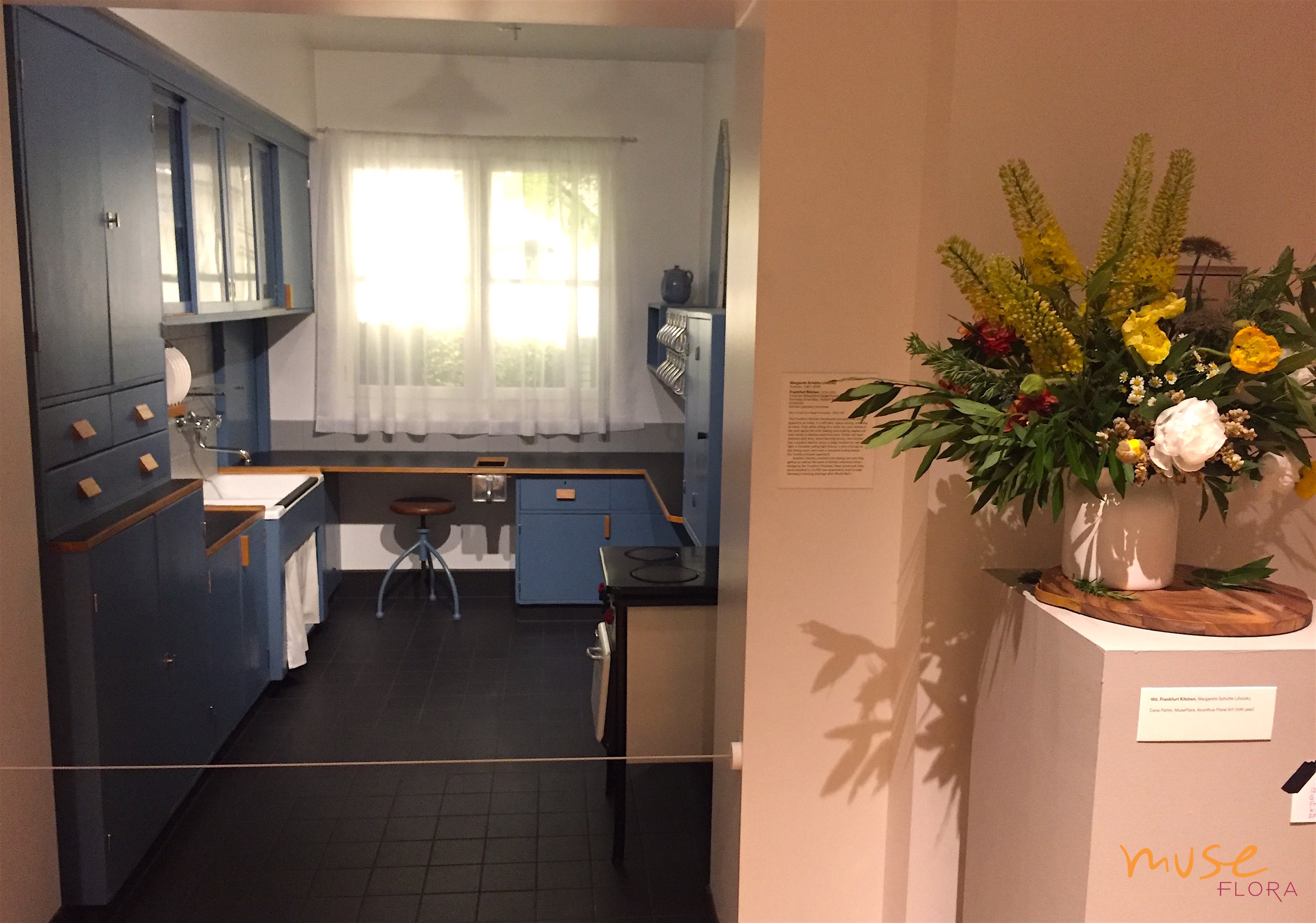"""Cana's floral interpretation of the """"Frankfurt Kitchen"""" during Art in Bloom 2018 is not a literal interpretation. That's what makes floral art so fun! Can you imagine the inhabitant sitting on the stool arranging it at the counter?"""