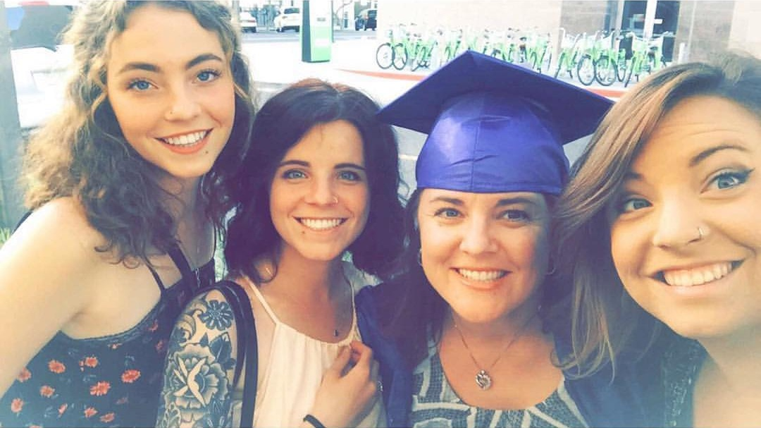 MY SERIOUS GRADUATION PICTURE WITH MY THREE ADULT DAUGHTERS.