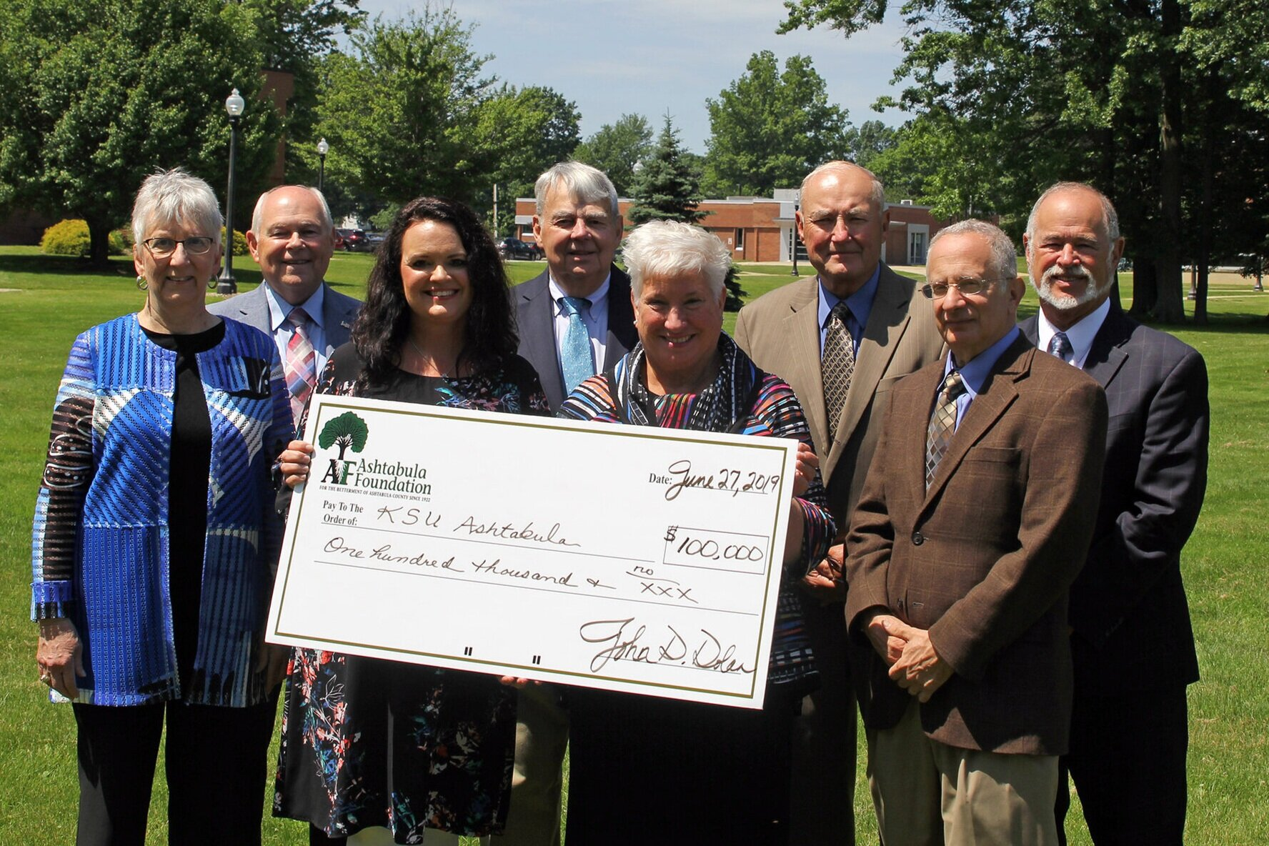 """PHOTO: Members of the Ashtabula Foundation present a ceremonial check in the amount of $100,000 to start an endowed fund in support of the Rising Scholars program at Kent State University at Ashtabula. Pictured are (left to right) Trustee and Past President Cheryle J. Chiaramonte, Trustee Roger A. Corlett, Associate Lecturer of Theater and Kent State Ashtabula Rising Scholars coordinator Natalie Huya, Board Secretary/Treasurer William W. """"Bud"""" Hill, Kent State Ashtabula Dean and Chief Administrative Officer Dr. Susan J. Stocker, Board President John D. Dolan, Trustee G. Richard Coblitz, and Trustee Dr. Jerome A. Brockway. ###"""