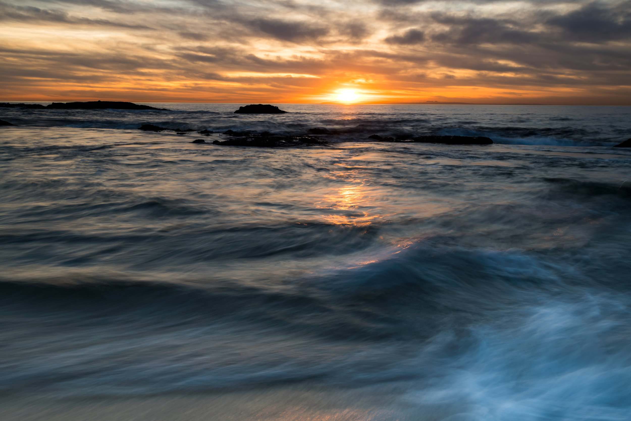 A long exposure captures movement in the waves durning a colorful sunset at Laguna Beach.