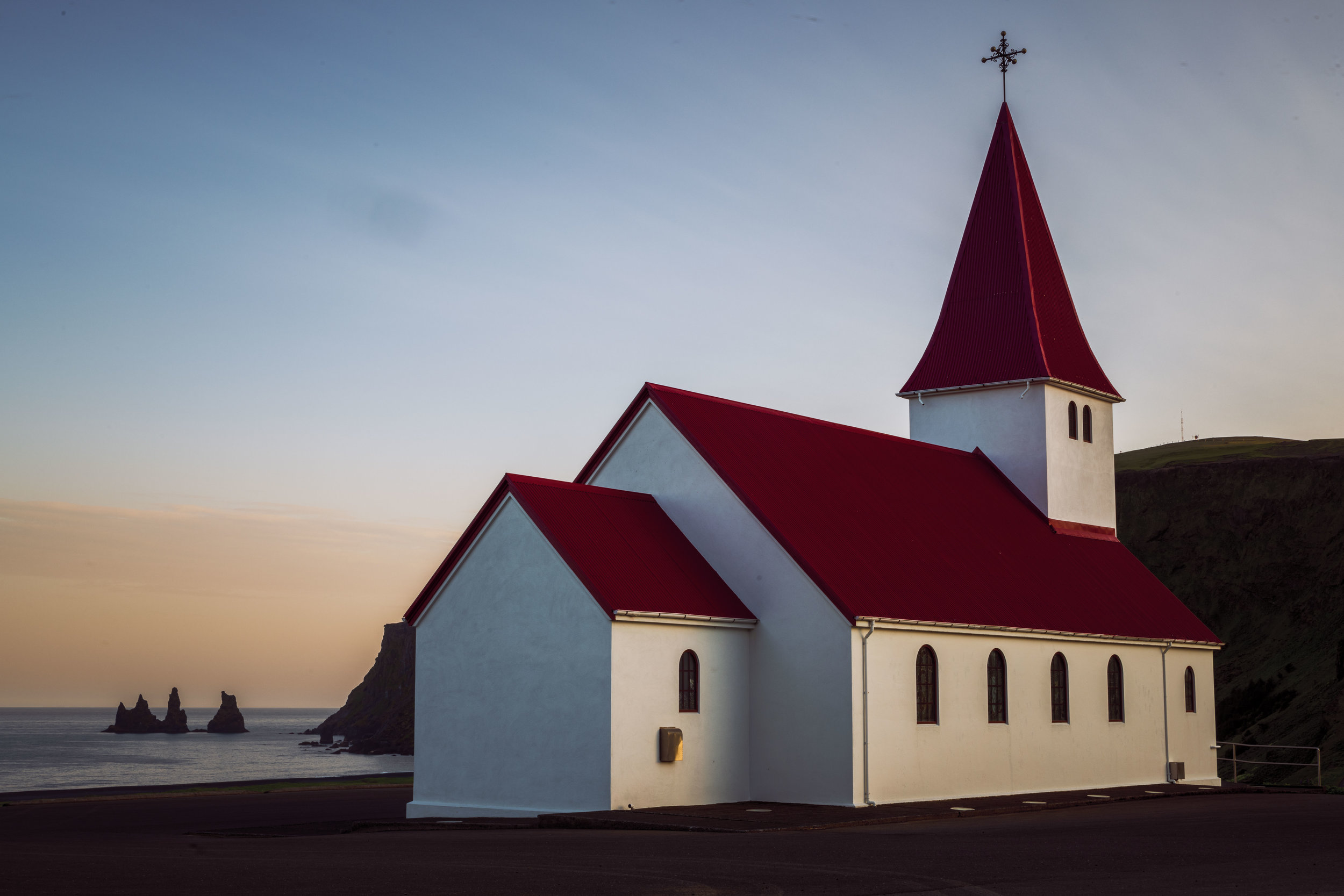 A midnight photo of a church in Vik with sea stacks in the background