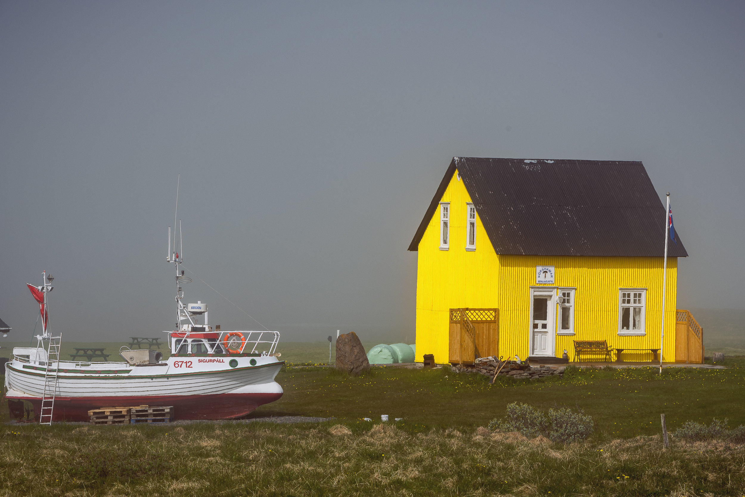 Yellow house and white boat along the norther coast of Iceland
