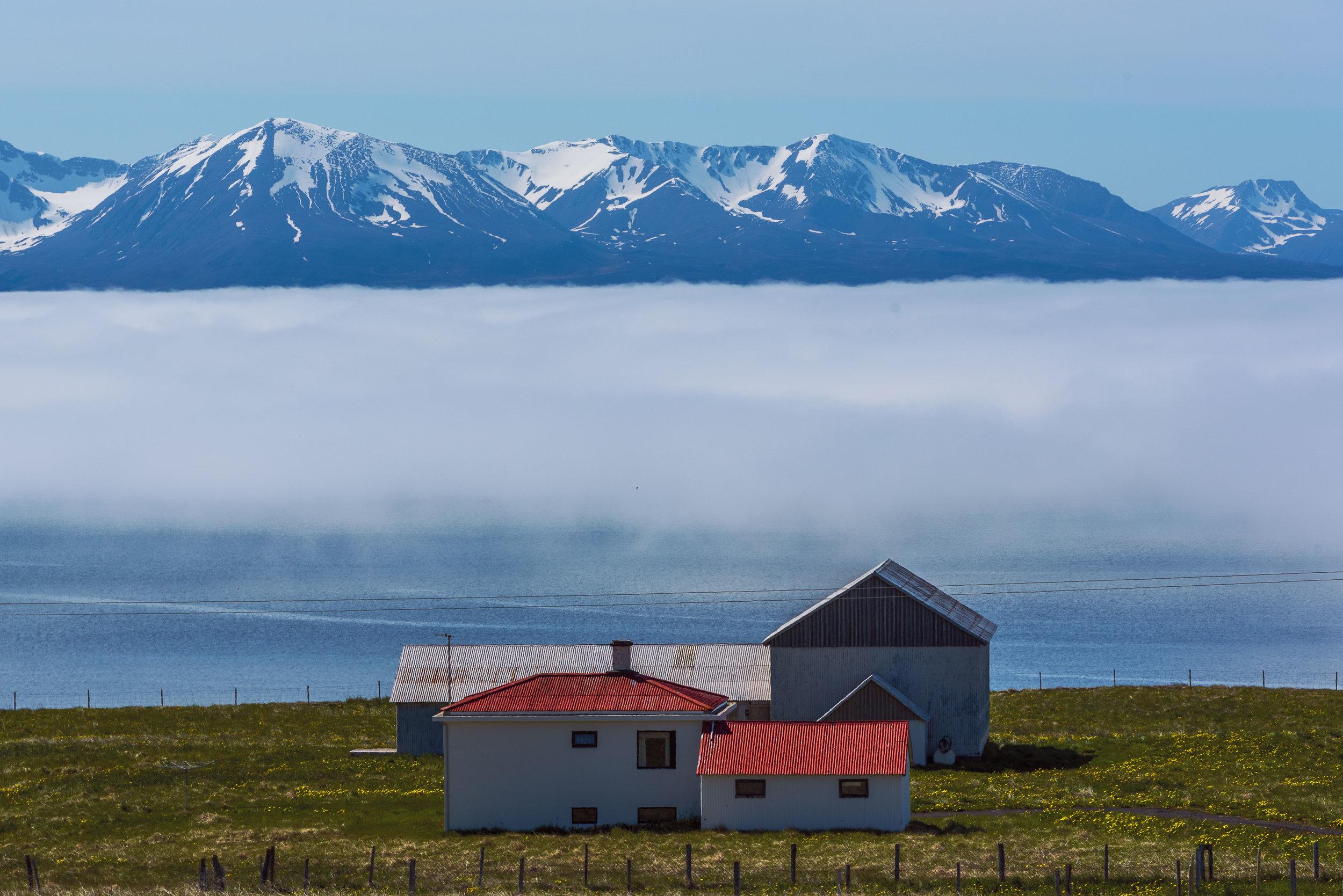 A layer of fog sets over the bay near Húsavík