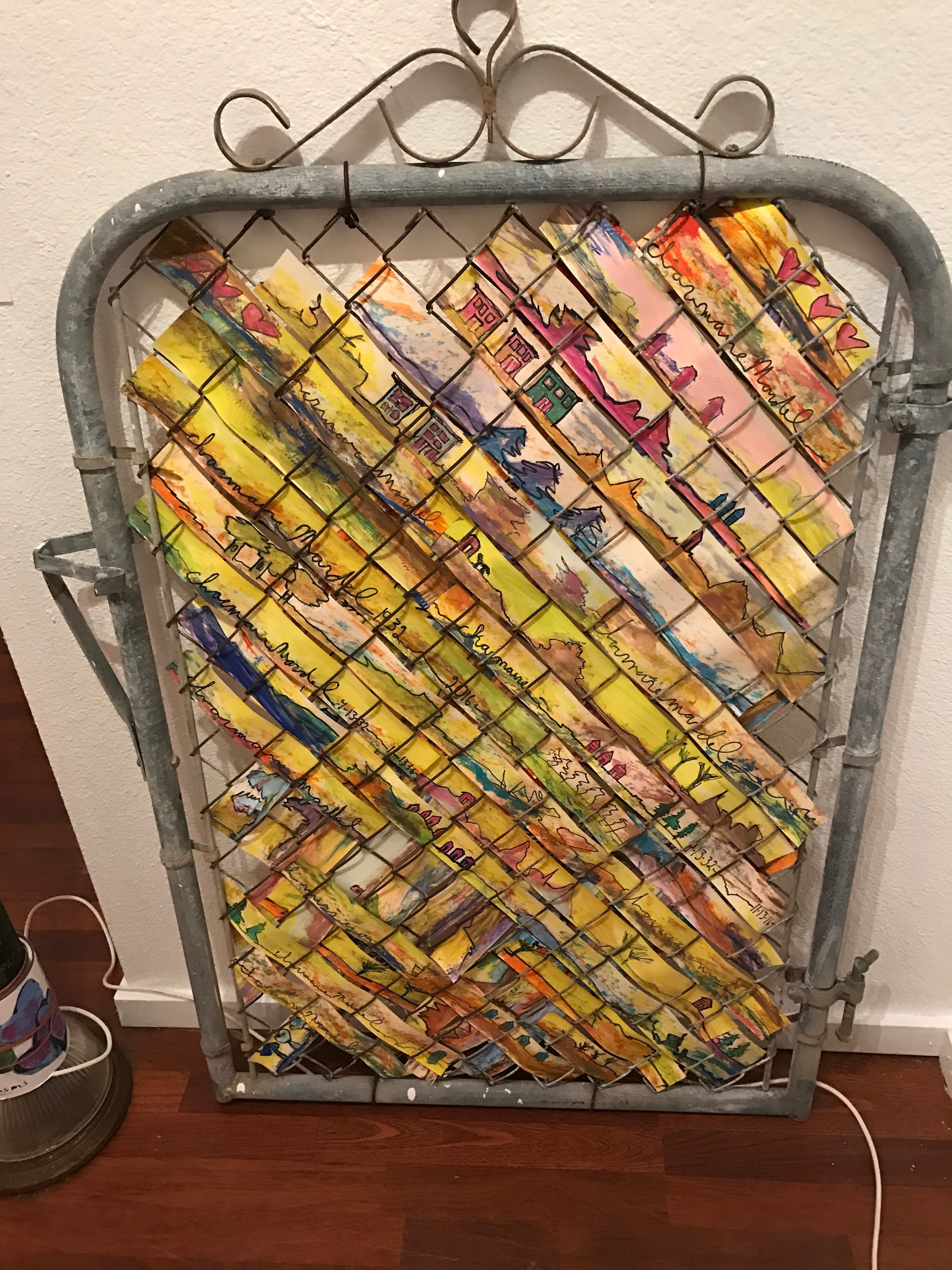 Vintage metal gate is woven with tempera on paper with landscape scenes and family mementos