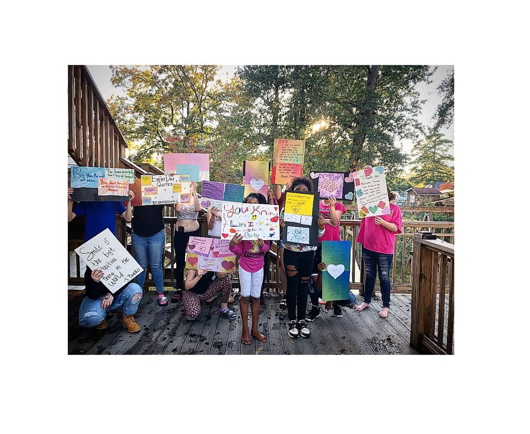 Photo Caption: A group of amazing children holding up inspirational and encouraging posters.