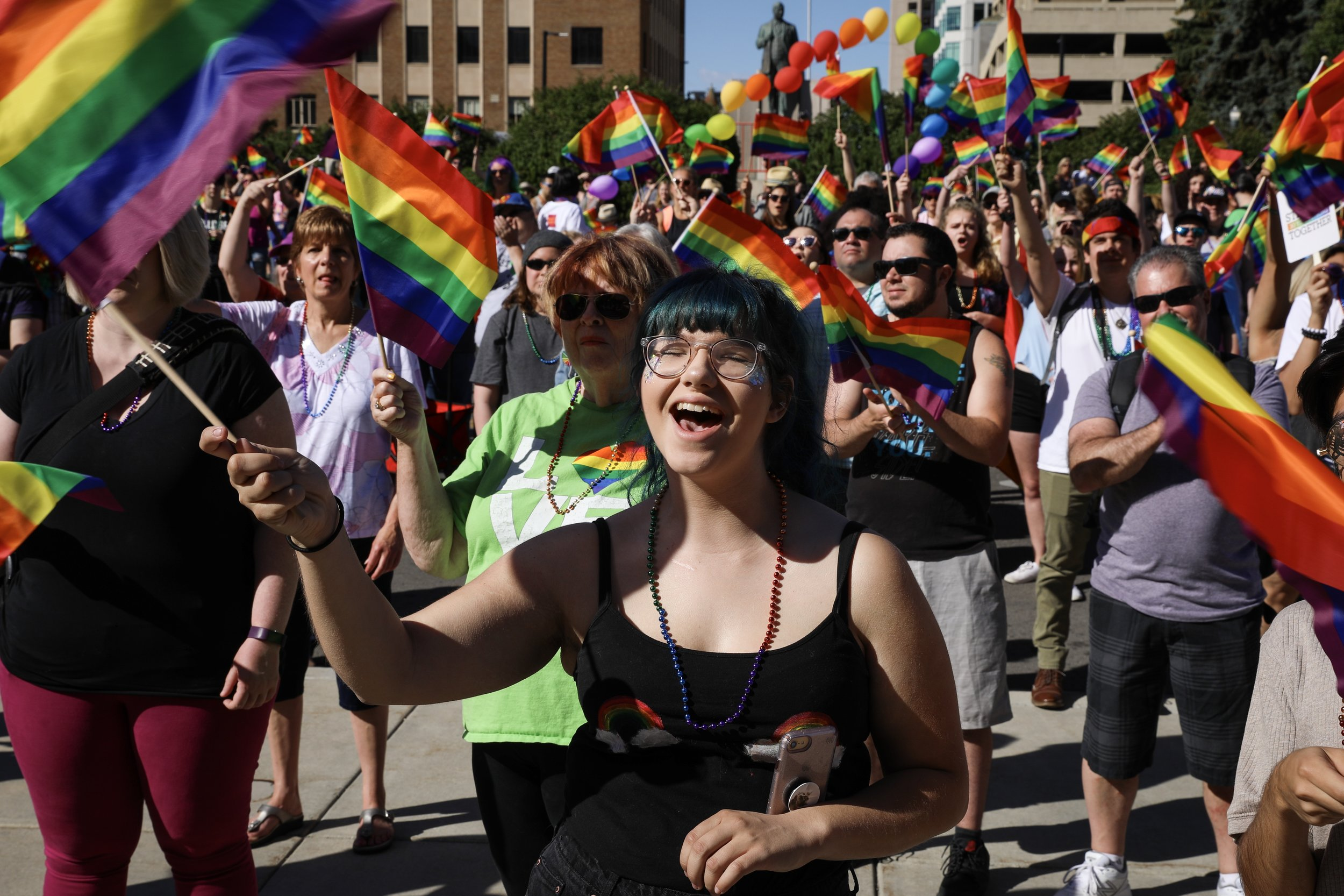 Emily Talbot, center, waves a rainbow flag to support a speaker during a rally at 2018 Boise Pride Festival in downtown Boise on Saturday, June 16, 2018. Talbot identifies herself as bisexual.