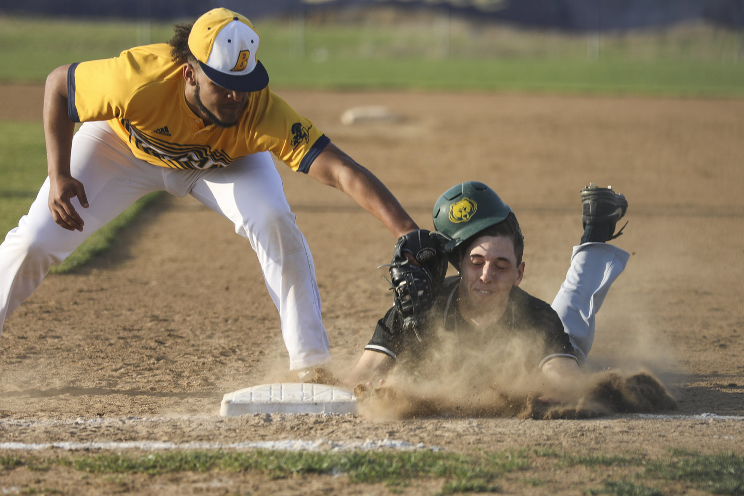 Battle's Jarel Hyler, left, attempts to tag Rock Bridge's Tony Pascucci during a game Tuesday at Battle High School in Columbia, Mo. the Spartans won the game 1-0 on a walk-off walk.