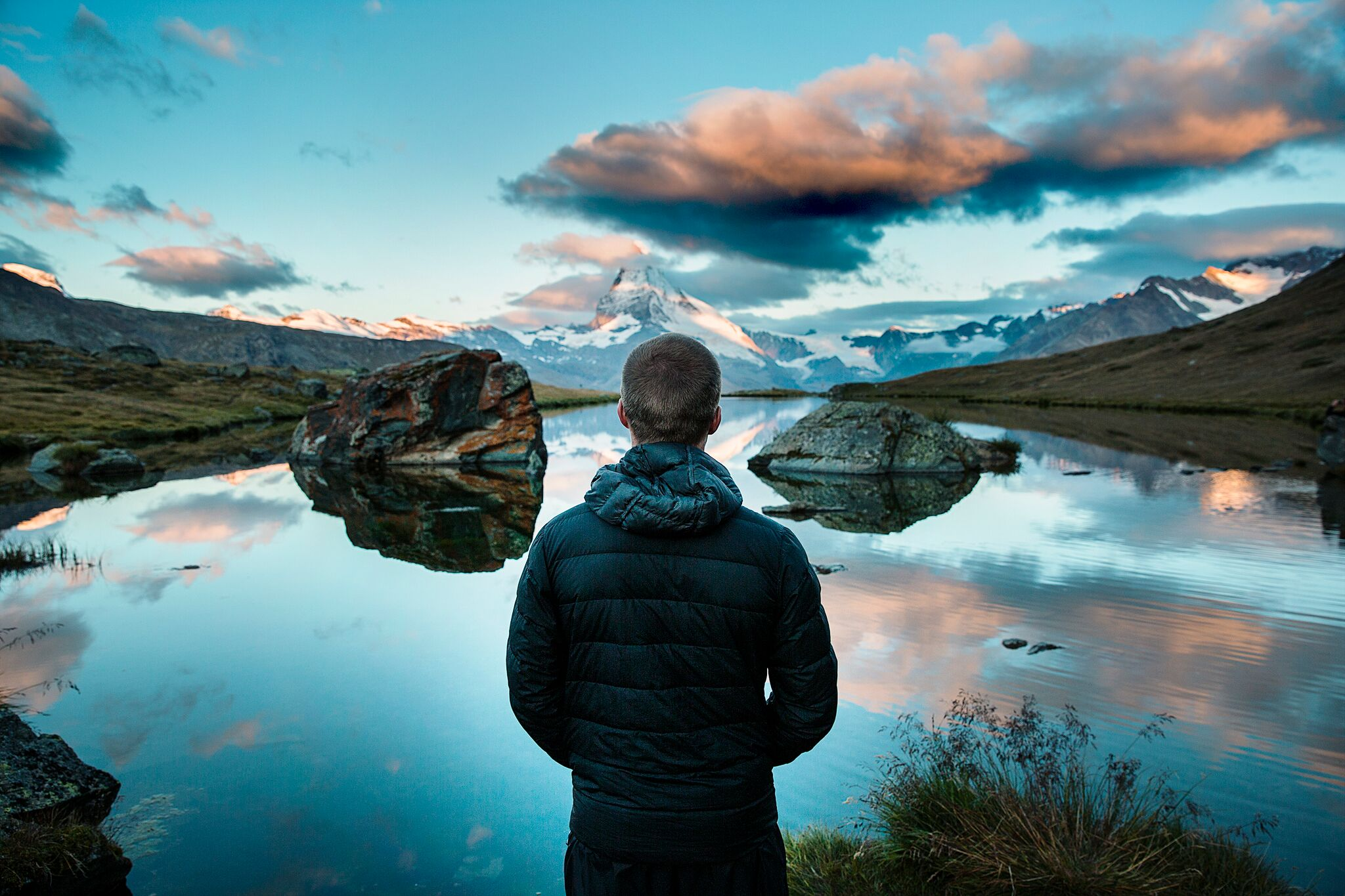 man looking out on lake and snowcapped mountain
