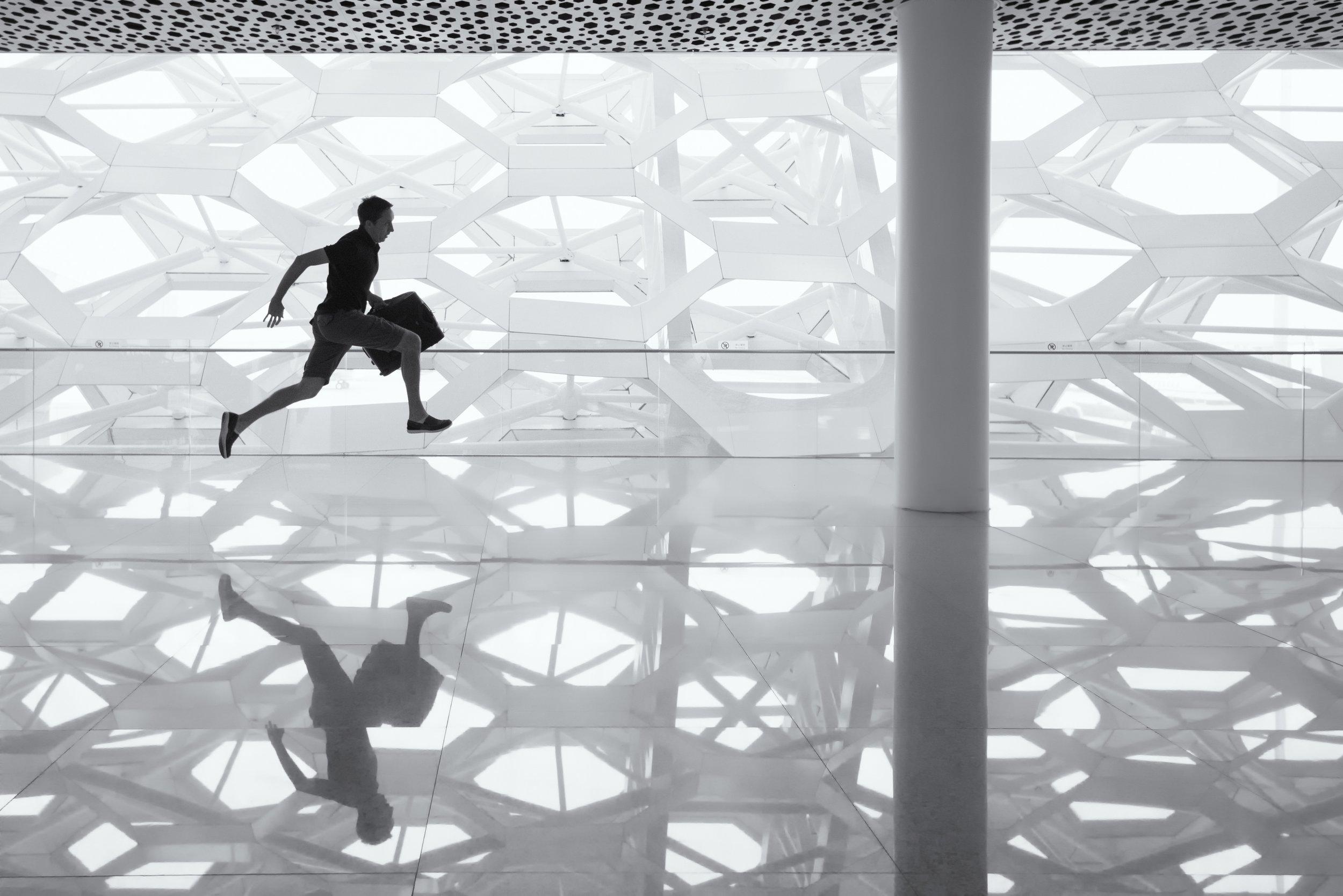 man with briefcase runs through office building