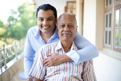 Indian adult son and father smile at camera and hug