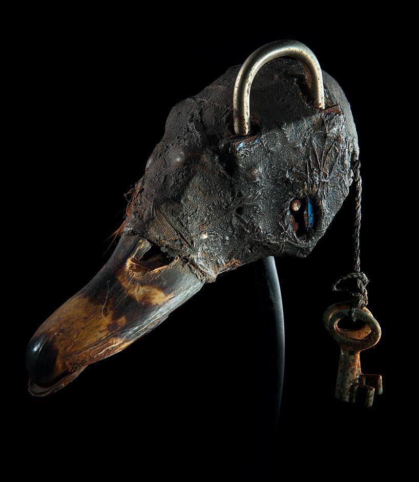 A Fon  vodun  (voodoo) object from Benin. Duck skull and bill, lock, keys, cloth, feather, clay, sacrificial patina.