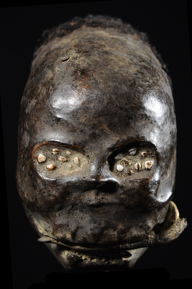 Trophy head covered in clay and human skin and hair. Collected in 1980 in southeast Nigeria. Height: 10 in (25 cm). Weight: 5.4 lbs (2,430 grams).